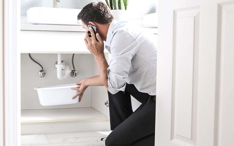 Image of a man in front of a leaking sink on the phone.