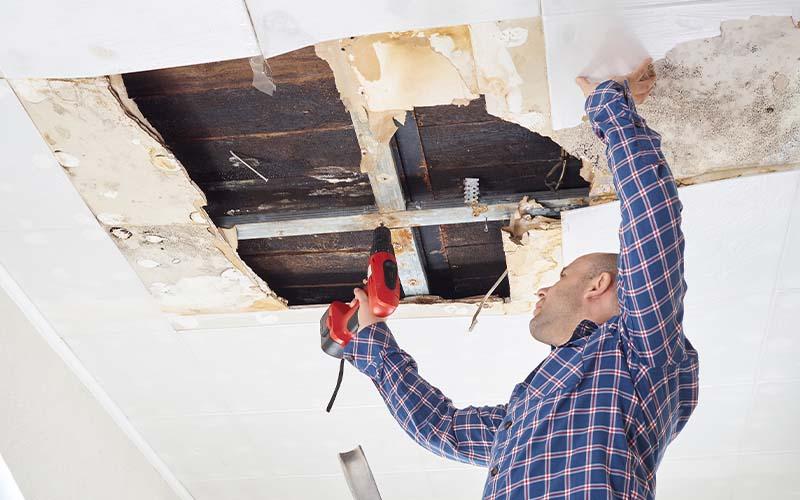 Image of man repairing damaged ceiling.
