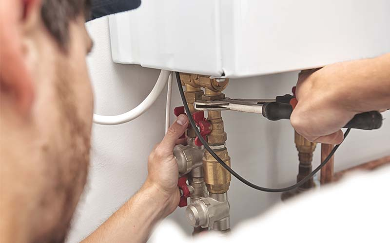 Photo of a man repairing a water heater.